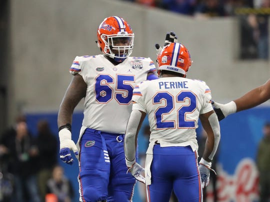 Dec 29, 2018; Atlanta, GA, USA; Florida Gators offensive lineman Jawaan Taylor (65) celebrates a run by running back Lamical Perine (22) in the first quarter against the Michigan Wolverines in the 2018 Peach Bowl at Mercedes-Benz Stadium. Mandatory Credit: Jason Getz-USA TODAY Sports