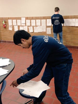 Bolton High Speech and Debate Club students Sansar Gupta (front) and Will Passman post schedules of rounds at the school's annual tournament Saturday.