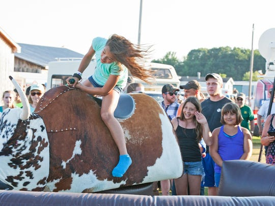 Ellie Prairie, 11, of Alburgh takes a spin on Gus the Mechanical Bull as friends and family watch her try to hold on during the 2015 Franklin County Field Days.