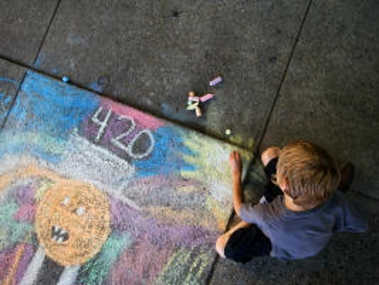 Seven-year-old Zane Driscoll, of Hanover, decorates Hanover's sidewalks in 2011. He said he was drawing a 'pumpkin guy with colors all around him.' (File -- The Evening Sun)
