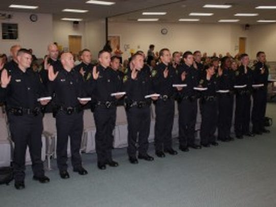 A new group of cadets are sworn in as Asheville police officers in 2012. Despite attempts to increase the number of black officers, the percentage of African Americans in the force has dropped since 1998.