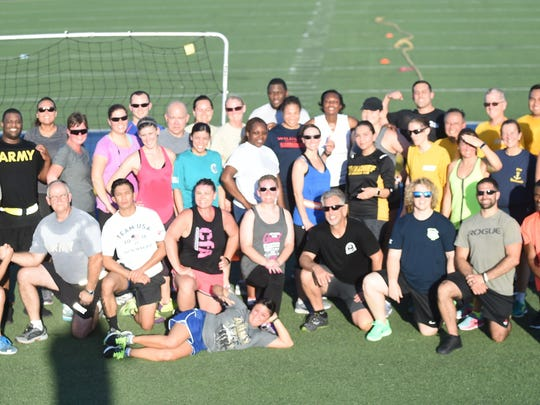Reservists and volunteers pose for a group after a P.T. session Tuesday at Bomber Stadium.