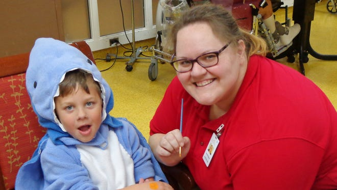 Activities Aide Laura Kinney is ready to paint the hand of one of the many children who dressed as ghouls, goblins, superheroes and, in this case, sharks that visited Towne Center for their Fall Festival.