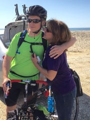 This May 14, 2016 photo shows Sloan Meadows, 21, of Northern Virginia, hugging his mom, Fran Meadows, on the beach at Assateague Island, Virginia, where he and buddy Zach Browning set out on bicycles for a two-month, cross-country trip to San Francisco to raise money toward medical research and awareness about Alzheimer's disease.