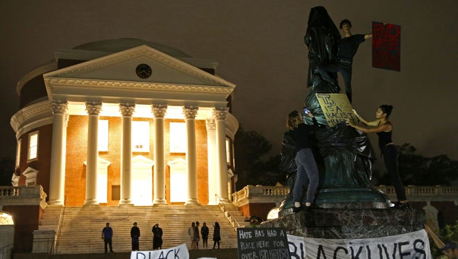 "Protesters cover a statue of Thomas Jefferson with black tarp and hold signs up in front of the Rotunda at the University of Virginia for the one month anniversary of the ""Unite the Right"" rally in Charlottesville Tuesday, Sept. 12, 2017."