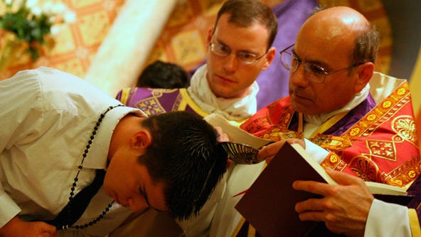 Shown at a baptism are Father Kenneth Walker (center), who was killed, and Father Joseph Terra, who was critically hurt.