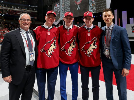 Coyotes draft picks Nate Schnarr, Mackenzie Entwistle and Cameron Crotty pose for photos with GM John Chayka (right) after being drafted on June 24.