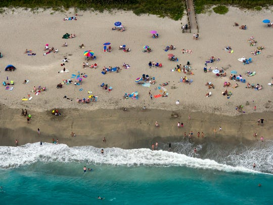 Visitors to Stuart Beach in 2013, enjoyed the warm weather in Stuart. President Donald Trump's proposed budget slashes the Environmental Protection Agency's budget by 31 percent. The EPA helps fund the BEACH Act, which is involved in testing coastal waters.