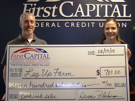Kevin Linden, vice president of finance at First Capital, presents a check for $701 to Jennifer Hitz, development director at Leg Up Farm.