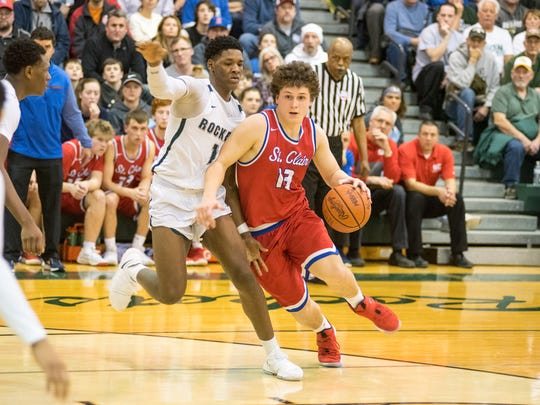 St. Clair High School's Ben Davidson (right) runs the ball around New Haven's Romeo Weems during the MHSAA Class B regional basketball semifinals at New Haven High School March 12.