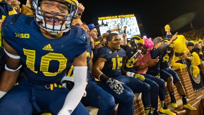 Michigan players celebrate with fans in the student section of Michigan Stadium after beating Penn State in Ann Arbor on Oct. 11, 2014.