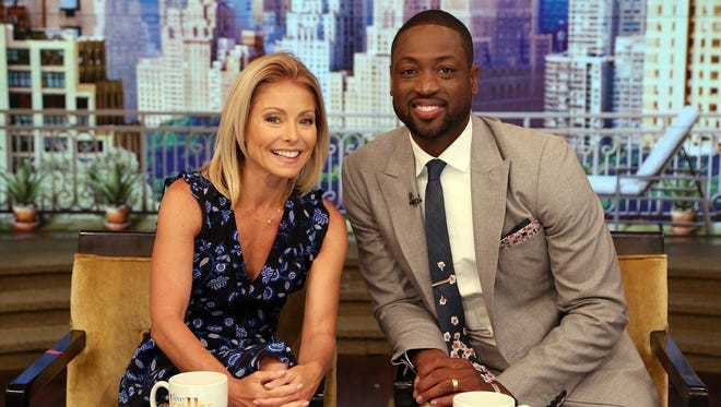 """TV host Kelly Ripa, left, and NBA basketball player Dwyane Wade pose during the production of """"Live Kelly"""" in New York, Thursday."""