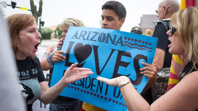 Lynnette Huston, right, and Susan Partlow argue Tuesday while waiting for President Barack Obama's motocade at Desert Vista High School in Phoenix.  Looking on is Michael Pomales.