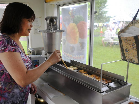 Emy Ahrendt makes mini doughnuts at her food truck, Emy's Mini Doughnuts, at Summertime by George! on July 15 at Lake George.