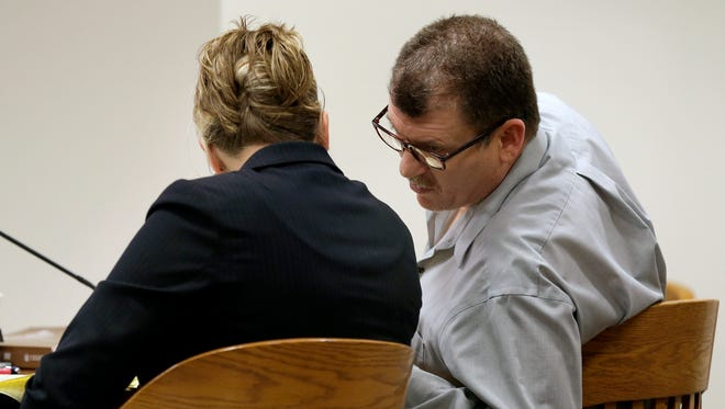Dennis L. Mitchell, 46, of Appleton, speaks with his attorney Amy Menzel during the second day of his trial in Outagamie County on January 7, 2015 in Appleton, Wis.
