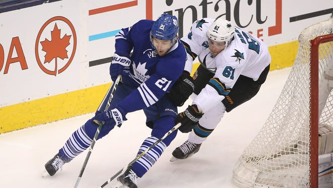 Toronto Maple Leafs left wing James van Riemsdyk (21) skates around the net with the puck as San Jose Sharks defenseman Justin Braun (61) bears down at Air Canada Centre.