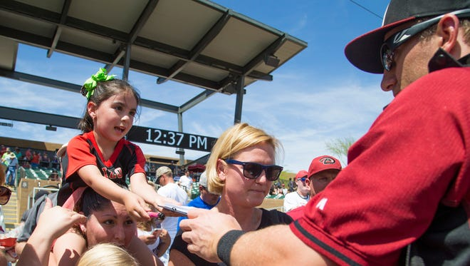 Ginger Morrow, 5, sits on her mom's, Jessica, shoulders while getting an autograph from Arizona Diamondbacks' Cliff Pennington before a spring training game against the Colorado Rockies at Salt River Fields at Talking Stick March 29, 2015.