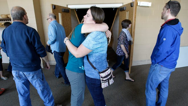 Krista Wager, on left, and Bethany Swanstrom hug outside the doors of a prayer service for victims at Calvary Bible Church on May 4, 2015 in Neenah, Wis. A shooting spree that resulted in four fatalities and one person injured occurred on the Fox Cities Trestle Trail bridge in Menasha Sunday night May 3, 2015 in Menasha.
