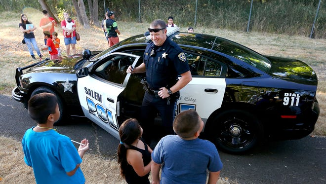 Salem Police Department Lt. Treven Upkes talks to a group of children during a National Night Out party for the Lansing Neighborhood at Livingston Park in 2015.