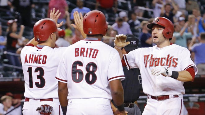 Arizona Diamondbacks center fielder A.J. Pollock (11) is greeted at the plate by Nick Ahmed and Socrates Brito after his three-run home run against the San Diego Padres in the 7th inning of their MLB game Tuesday, Sept. 15, 2015 in Phoenix, Ariz.