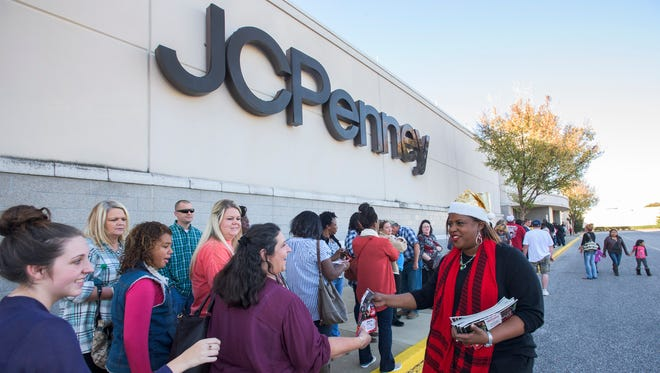 General Manager Bridie Clinkscales hands out sales papers to Thanksgiving Day shoppers as they line up outside of JC Penney at Eastdale Mall in Montgomery, Ala. on Thursday afternoon November 26, 2015.