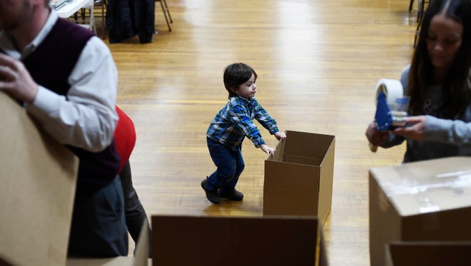 Elijah Krebs, 3, of Springettsbury Township, pushes a box across the floor as volunteers pack Valentine's Day care packages for troops serving overseas at Alert Fire Hall in Emigsville.