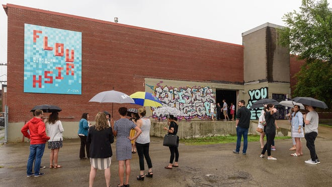 """People stand outside to see the mural """"Flourish"""" on the side of Louisville Visual Arts' space after the announcement of LVAs' new Mural Art Program, a collaboration between LVA, Center for Neighborhoods and Louisville Metro at their offices at 1538 Lytle Street in the Portland neighborhood. July 28, 2016"""