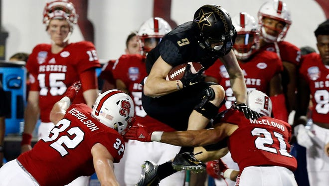 Vanderbilt wide receiver Caleb Scott (9) tries to hurdle over North Carolina State cornerback Nick McCloud (21) and linebacker Riley Nicholson (32) in the second half of the Camping World Independence Bowl NCAA college football game in Shreveport, La., Monday, Dec. 26, 2016. North Carolina State won 41-17.