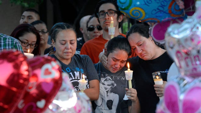 In this Aug. 25, 2016 photo, from left to right, Nicole Maldonado, Myriah Flores, and her mother Sharlene Benavidez attend a candlelight vigil for 10-year-old Victoria Martens at the apartment complex, in Albuquerque, N.M., where the young girl lived and was killed. Martens was strangled to death on her 10th birthday before she was dismembered and her remains set on fire, according to an autopsy released months after police uncovered the sexual abuse they say she suffered at the hands of her mother and others leading up to her killing.