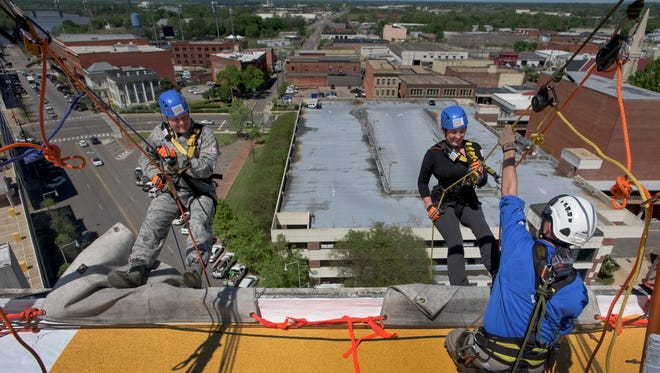 Brian Copper, left, and Kim Traff rappel off of the 40 Four Building as part of Over the Edge, a fundraiser for Hope Inspired Ministries, in downtown Montgomery, Ala., on Friday March 31, 2017. The event will run from 9am till 6pm on Saturday.