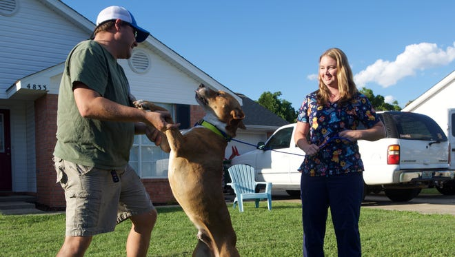 Gulf Breeze residents John and Sarah Dukes celebrate the return of the family dog, Copper, on Wednesday, May 24, 2017. Copper disappeared from the family home last month but was found in Okaloosa County with a gunshot wound to the head.