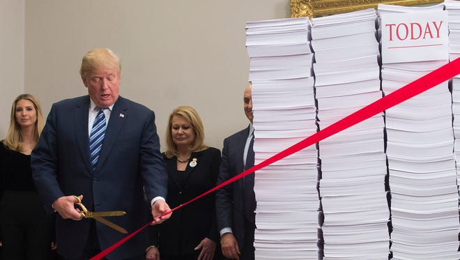 President Trump holds gold scissors Thursday as he cuts a red tape tied between two stacks of papers representing the government regulations of the 1960s and the regulations of today.