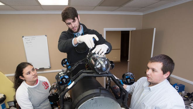 Kiara Korkuc, Zack Pennington, and Brian Arnold work on completing a next-generation prototype to catch Lionfish using an underwater remotely operated submersible.