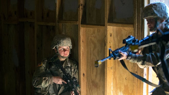 In this Oct. 4, 2017, photo, A female U.S. Army recruit practices building clearing tactics Oct. 18, 2017, with male recruits at Fort Benning in Georgia. She is one of a handful of women training to become infantry soldiers.