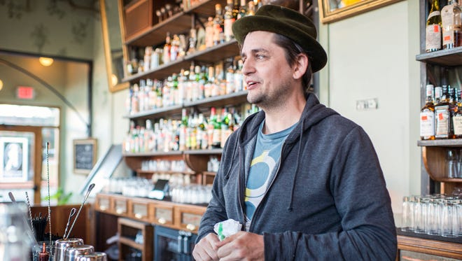 Charlie Hodge stands behind the bar at Sovereign Remedies in Asheville.
