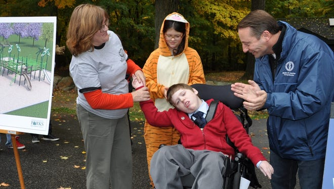 From left: Elizabeth Oram and 12-year-old twins Emma and Spencer with Westchester County Executive Robert Astorino.
