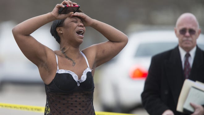 """Renetta Scott talks with IMPD officers after learning that her brother was killed in a possible domestic shooting in the 2600 block of Hawthorne Lane, Tuesday, March 17, 2015. """"My brother is gone,"""" Scott said."""