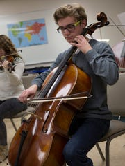 School for Strings student Zachary Johnson, 17, plays the cello during a group rehearsal Thursday, Feb. 18, 2016 at Faith Lutheran Church in Port Huron. Students from the school will be performing at the Stirling Bridge International Youth Festival this summer in Scotland.