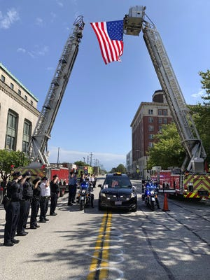 On Sept. 5, a hearse bearing the body of Det. James Skernivitz, passes under an arch made by two Cleveland Division of Fire fire engines, as it proceeds to the funeral home under police escort.
