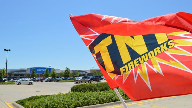 A flag flies outside of a TNT fireworks stand in the Walmart parking lot on June 27 in Iowa City.