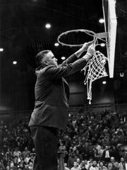 Marion Crawley cuts the net off of the basketball hoop after a state tournament win in 1959.