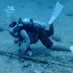 A diver is shown assessing an undersea cable in the Saipan Channel.