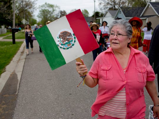 Carmen Medrando, of Port Huron, carries the flag of Mexico during the Cinco de Mayo parade Saturday, May 9, 2015 in South Park in Port Huron.
