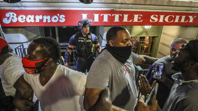 Protesters surround Louisville Metro Police Department officer Galen Hinshaw in front of Bearno's restaurant on Thursday, May 28, 2020 in Louisville, Kentucky.  Five strangers, including Julian De La Cruz, Ricky McClellan, (far right) and Darrin Lee Jr. (center, right), linked arms to keep the crowd from getting to Hinshaw.