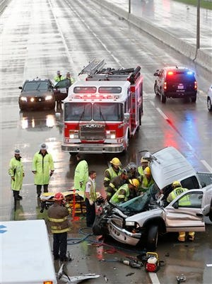 First responders work to remove a passenger of a truck involved in an accident on Interstate 35 during severe weather in Moore, Okla., Wednesday, May 6, 2015. I-35 southbound is closed behind the accident. (AP Photo/Sue Ogrocki)