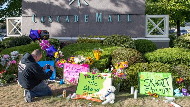 Chris Nelson of Burlington, Wash., takes a picture of a memorial at Cascade Mall on Sunday Sept. 25, 2016,