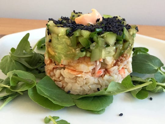 Spicy California Shrimp Stack has avocado, rice and black sesame seeds. It's set on a bed of watercress.
