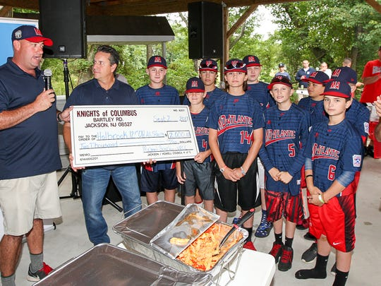 Holbrook Little League officials accept a $2,000 check
