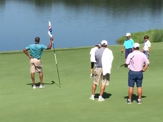 Dan Mullen watches his son sink a putt.