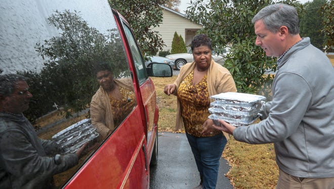 Greg Skipper, right, executive director for Calvary Home for Children in Anderson, carries packaged meals Tuesday for Sallie Parker, left, a house mother over seven children served by the home in Anderson.
